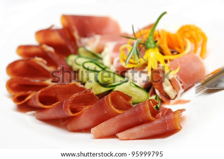 Slices of prosciutto rolled up and arranged with cucumber and papper