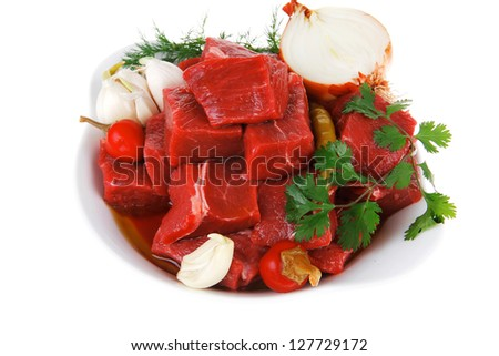 slices of raw fresh beef meat fillet in a white bowls with garlic and red peppers isolated over white background