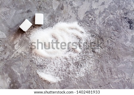 Slices of refined sugar and granulated sugar sand on the table. Top view