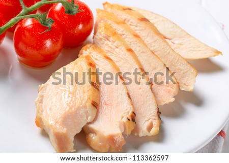 Slices of roasted turkey breast with cherry tomatoes and herb on a plate