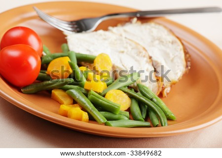 Slices of roasted turkey with vegetables closeup