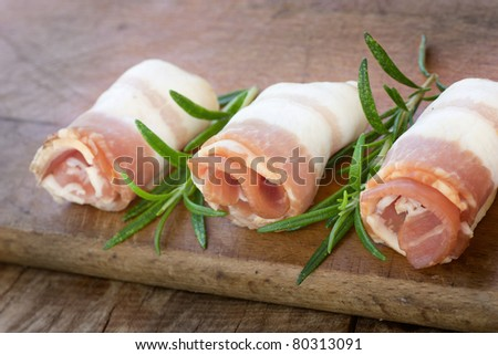 Slices of rolled bacon with rosemary