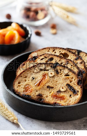 Slices of rye bread with hazelnuts and dried fruit like apricots, raisins and plums #1493729561