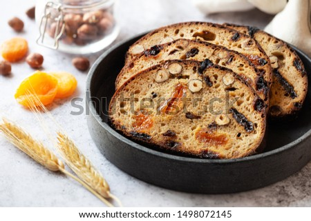 Slices of rye bread with hazelnuts and dried fruit like apricots, raisins and plums #1498072145