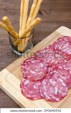 Slices of salami on cutting board and bread sticks on wooden table top