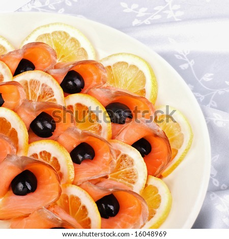 Slices of salted salmon fish on the plate with lemon and black olives