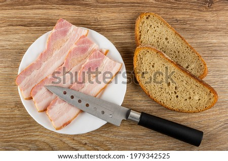 Slices of smoked brisket, kitchen knife in white plate, slices of bread on wooden table. Top view Photo stock ©