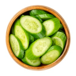 Slices of snack cucumbers, in a wooden bowl. Heap of diagonally cut fresh, small, young and whole cucumber fruits. Cucumis sativus, a vegetable. Close-up, from above, isolated, over white, food photo.