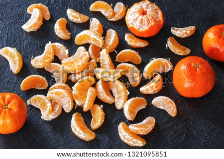 slices of tangerines and whole tangerines on the table. background with tangerines. #1321095851