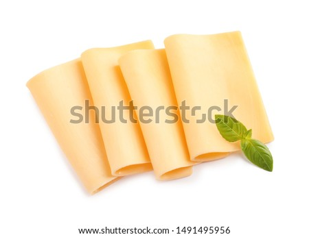 Slices of tasty cheese with basil on white background, top view