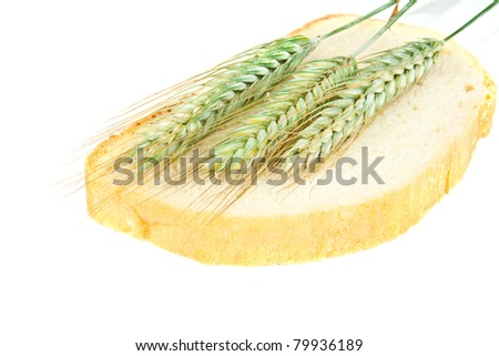 Slices of the cut bread. Bread baked with ears of wheat, isolated on a white background