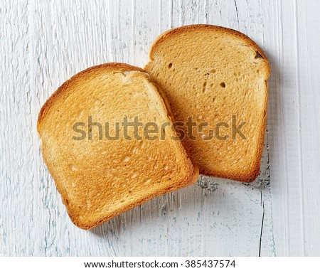 Slices of toast bread on wooden table, top view