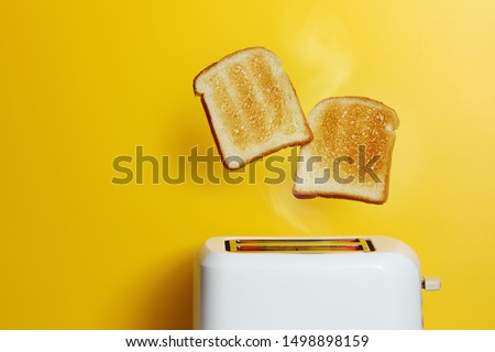 Slices of toast jumping out of the toaster against yellow background. #1498898159