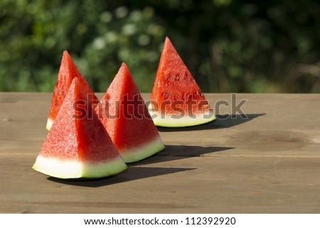 slices of watermelon on wooden table, mediterranean garden background