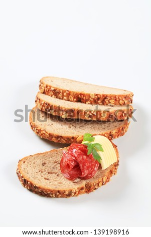 Slices of wheat bread with butter and salami