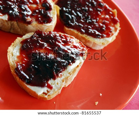 slices of white bread with plum marmalade on red plate