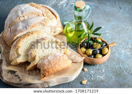 Slices of white homemade bread on the wooden cutting board. Olive oil bottle and olives in the wooden bowl on the dark background.  Foto d'archivio ©