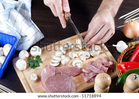 Slicing of fresh mushrooms on wooden board - stock photo