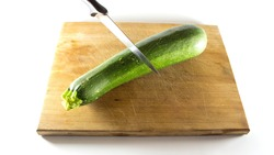 Slicing with a knife of Green regular Zucchini, courgette on a wooden Cutting board - isolated