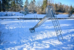 slide at a bathing place covered in snow february 2021