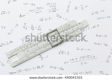 slide rule lying on a piece of paper with handwritten calculations