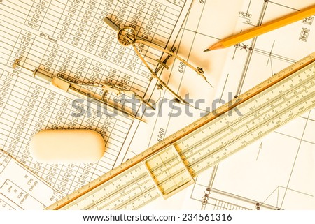 Slide rule with diagrams and drawing tools on the table. In yellow tone