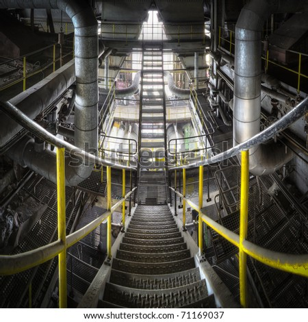 Sliding down the stairs with our eyes, floating between the lines to go down to the next floor. A great overlook of a metal constructed staircase inside the belly of this huge power plant.