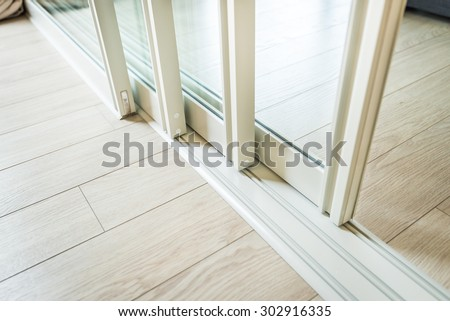 Photo of  sliding glass door detail and rail embed in wooden floor