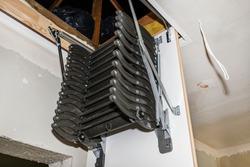 Sliding metal stairs to the attic in the ceiling, an open hatch and compound stairs, modern look.