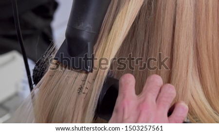 Sliding shot of a professional hairdresser blow drying hair of his client
