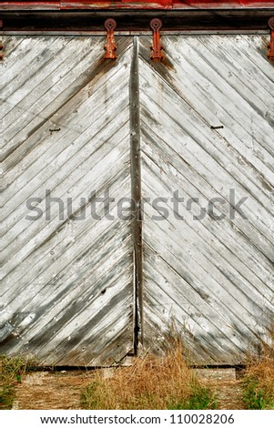 Sliding white slatted entry door into old red barn showing its age in wear and tear