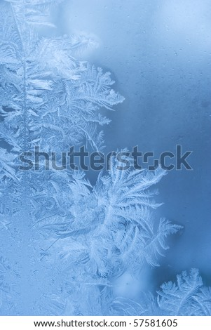 Slightly blurred beautiful frostwork on a window glass (as an abstract winter background)