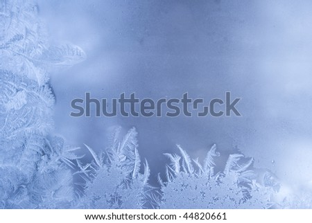 Slightly blurred beautiful frostwork on a window glass (with empty space for your text or image)