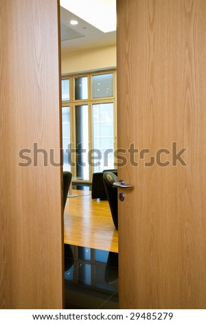 Slightly opened wooden door with the metal handle close up