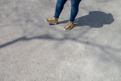 Slightly overweight Woman with skinny blue jeans and golden white fashion sneakers waiting standing on a walkway on a nice sunny day with shadow and tree limb shadow