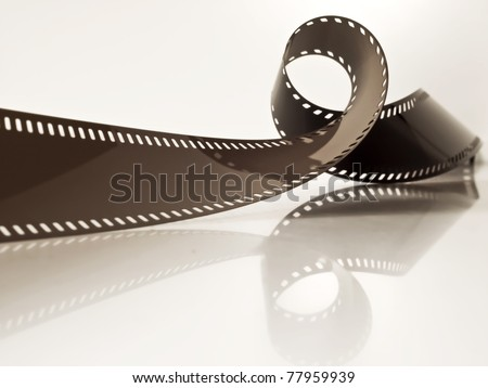 slightly rolled undeveloped film strip on a glossy surface