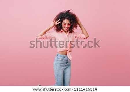 Slim african female model in vintage denim pants expressing happiness. Indoor photo of glamorous shapely girl in casual attire laughing near pink wall. #1111416314