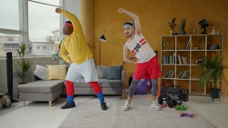 Slim and chubby funny fitness guys doing warm-up stretching exercises together at home. Sports freaks. Concept of friendship, team, humor.