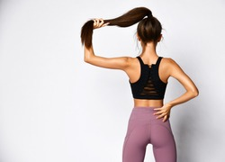 Slim athletic brunette woman in sportswear pants and sports bra top stands back to us holding ponytail in hand on gray  background