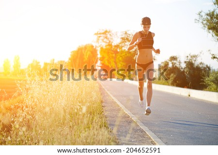 Slim athletic girl at high speed running down the road along beautiful field, evening run outside, beautiful sunset light, fitness and healthy lifestyle concept