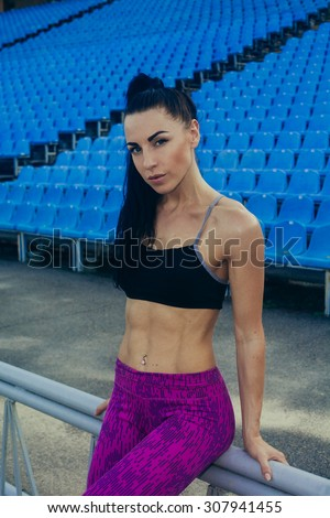 Slim athletic woman with dumbbells in the stadium. Sporty sexy girl with flat belly workout, outdoors