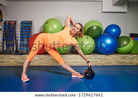 Slim athletic young woman in sportswear does exercises using weight in fitness club. Female home workout.