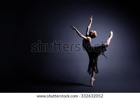 Slim ballerina is dancing in the dark