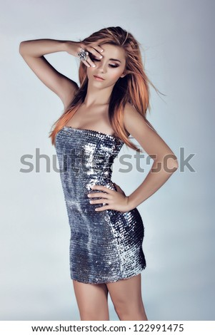 slim beautiful woman with long blowing hair on studio background wearing a silver sequin minidress
