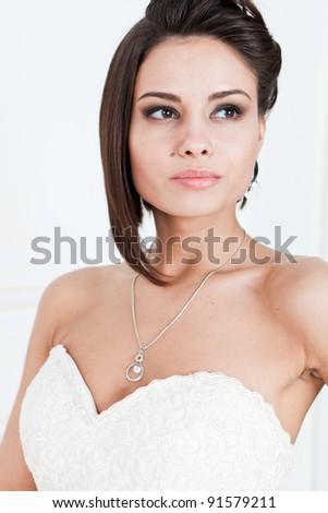 Slim beautiful woman with short hair wearing luxurious wedding dress over white studio background
