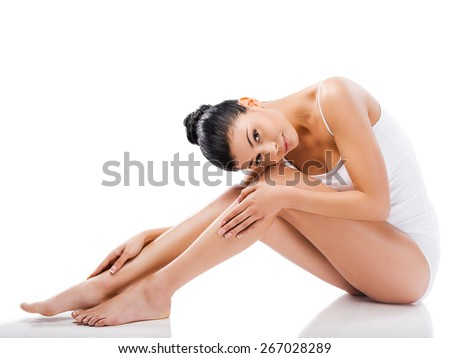 Slim beauty. Beautiful young woman looking at camera and holding hands on her legs while sitting against white background