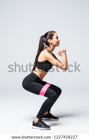 slim blonde woman doing squats with fitness loop band isolated on white background