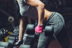 Slim, bodybuilder girl, lifts heavy dumbbell standing in front of the mirror while training in the gym. Sports concept, fat burning and a healthy lifestyle.