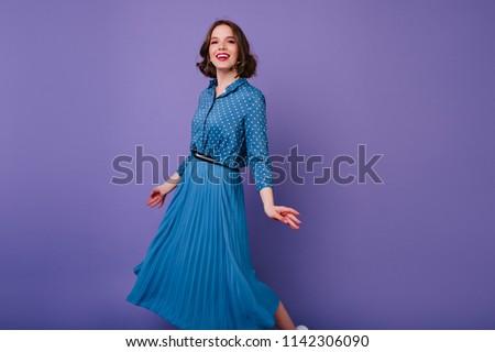 Slim brunette woman dancing on purple background with happy face expression. Debonair european girl in long skirt posing in studio.