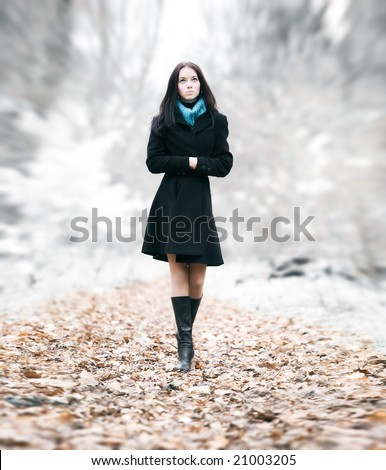 Slim brunette woman walking in a park. Special background blur effect.